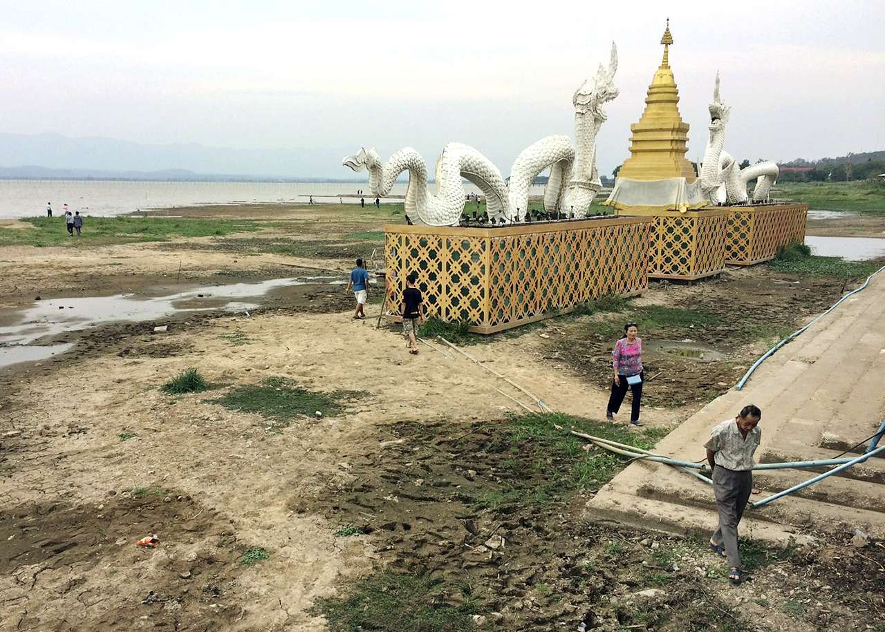 epa05238722 A photo made available on 01 April 2016 shows Thai villagers walking on drought parched land near the dried up Phayao Lake in Phayao province, northern Thailand, 29 March 2016. Thailand is facing a water shortage caused by the worst drought in decades, exacerbated by the El Nino weather phenomenon and combined with seasonal hot weather. Water reservoirs in Thailand are significantly low while the water level in the country's biggest dams are lower than 10 percent capacity, and other major reservoirs are below 50 percent of their water capacity. The drought has affected the agriculture across country, bringing Thailand's economic growth down by 0.6 percent, to 0.85 percent. EPA/CHAICHAN CHAIMUN